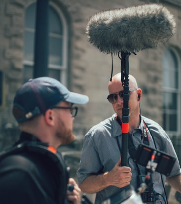 A man holding a Boom pole with a shotgun-mic attached on to it via a pistol grip mount. The mic is probably on a shockmount but is covered in a furry wind muff. The mic is connected to a field recorder via XLR cable.